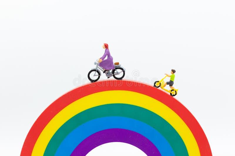 Miniatyrfolk: Mamma och ungar som cyklar på regnbågen Bildbruk för att vara bra modell, familjbegrepp royaltyfria bilder
