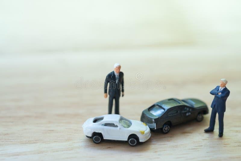 Miniatyrfolk: Man för två chaufförer som argumenterar efter en biltrafikolyckasammanstötning arkivbilder