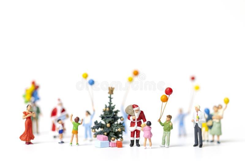 Miniatyrfolk: Santa Claus innehavgåva för lycklig familj arkivbilder