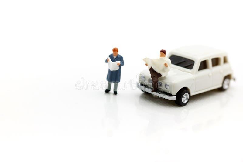 Miniatyrfolk som läser och sitter på bilen genom att använda som bakgrund royaltyfri foto