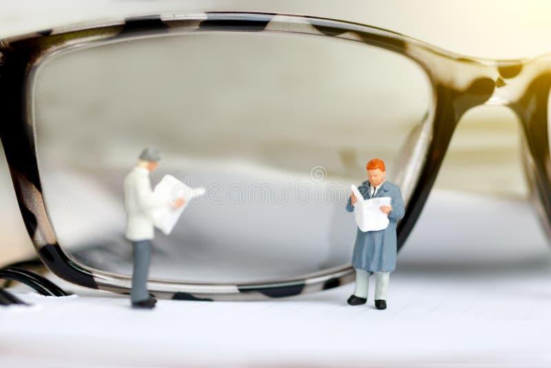 Miniatyrfolk som läser och står på boken med exponeringsglas genom att använda som bakgrund, royaltyfri fotografi