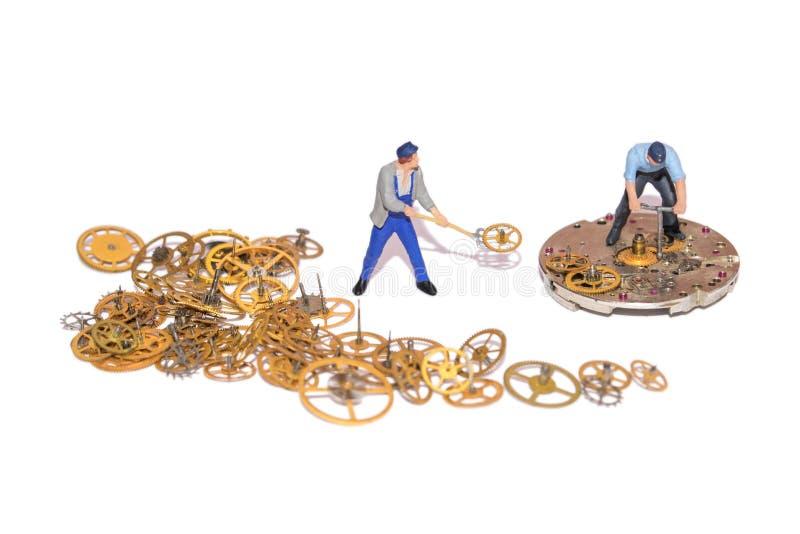 Miniatyrfolk som reparerar urverk Teamwork Hjälp i arbetet Funktionsdugliga anställda En hög av kugghjulet Isolerade kugghjul och arkivbilder