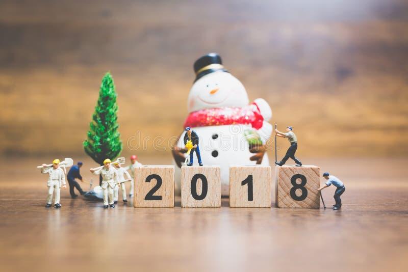 Miniatyrfolk: träkvarter nummer 2018 för arbetarlagbyggnad royaltyfri bild