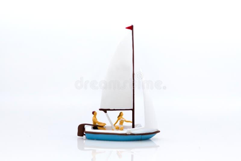 Miniatyrfolk: Turister med att segla för sportar Bildbruk för loppaffärsidé royaltyfri bild