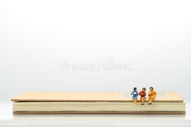 Miniatyrfolkaffärsmansamtal, smuttkaffe sitta på anteckningsboken genom att använda som bakgrundsaffärsidé med kopieringsutrymme arkivbild