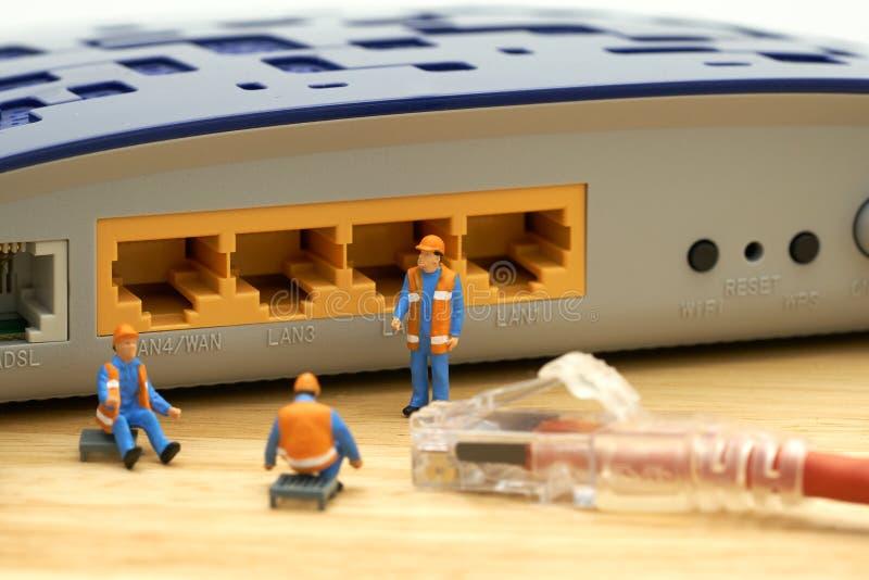 MiniatyrfolkbyggnadsarbetareLAN anslutning eller förbinder t royaltyfri bild