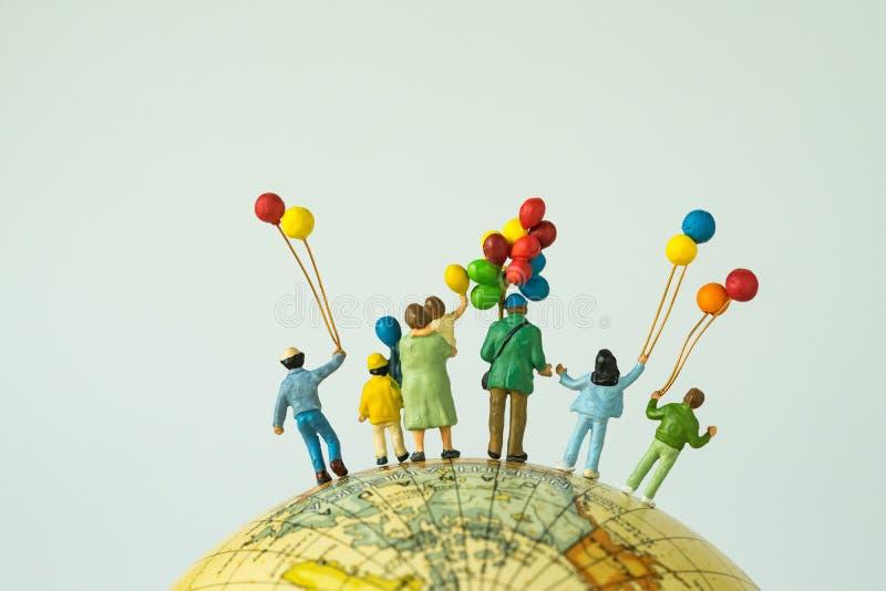 miniatyrfolkdiagram tillbaka sikt av den hållande ballooen för lycklig familj arkivbilder