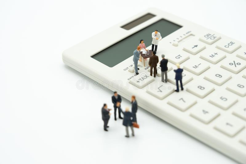 Miniatyrfolket betalar köårsinkomstSKATT för året på räknemaskinen använda som bakgrundsaffärsidé och finans arkivbild