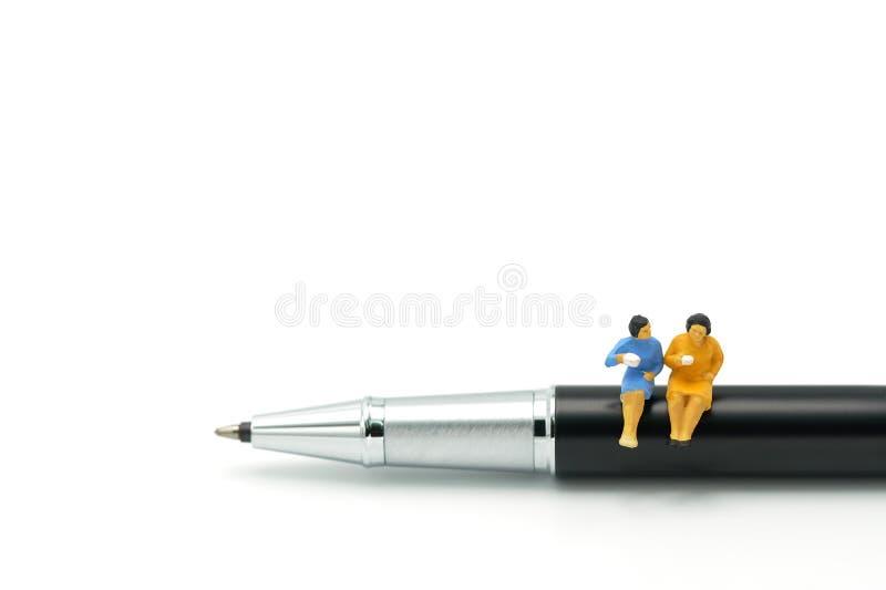 Miniatyrfolket sitter på pennorna, utbyter idéer, diskuterar problem genom att använda som bakgrundsaffärsidé och finansierar beg royaltyfria foton
