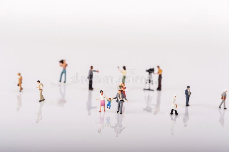 Miniatyrfolkfolkmassa över vit bakgrund arkivfoton