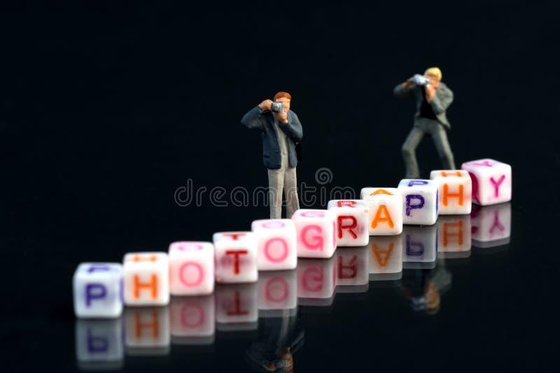 Miniatyrfotografer som tar bilder bak en grupp av bokstäver som bildar ordstavning royaltyfri foto