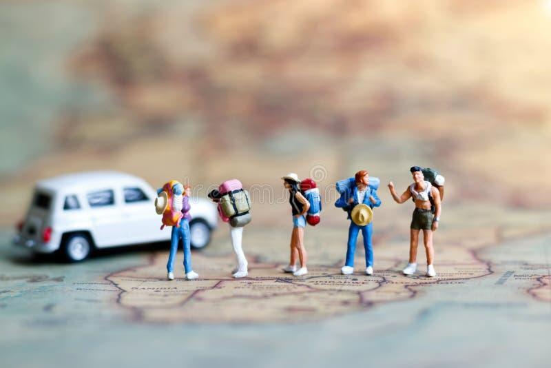 Miniatyrfotvandrare på översikt med bilen, begrepp av loppet omkring royaltyfri bild