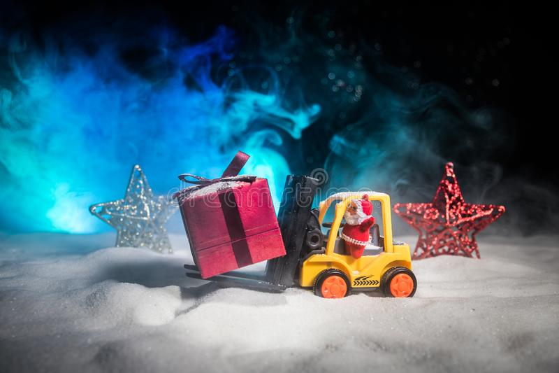 Miniatyrgåvaask vid gaffeltruckmaskinen på snö, beslutsam bild för julferie och för gåvaberöm för lyckligt nytt år begrepp royaltyfri foto