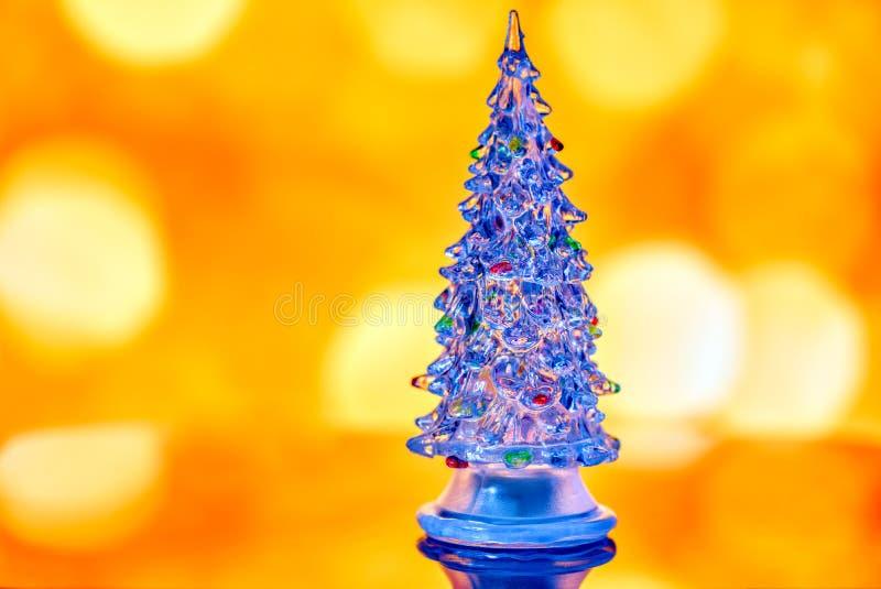 Miniatyrgenomskinlig julgran som isoleras på guld- bokehli arkivfoton