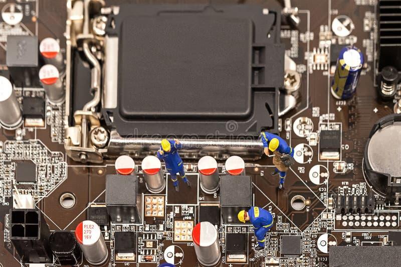 Miniatyrgruppen iscensätter kontroll av datorprocessorn med chipen och att reparera royaltyfri fotografi