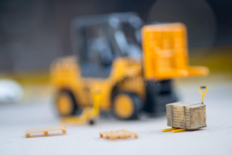 Miniatyrgul leksakgaffeltruck och miniatyrpalettlastbil fotografering för bildbyråer