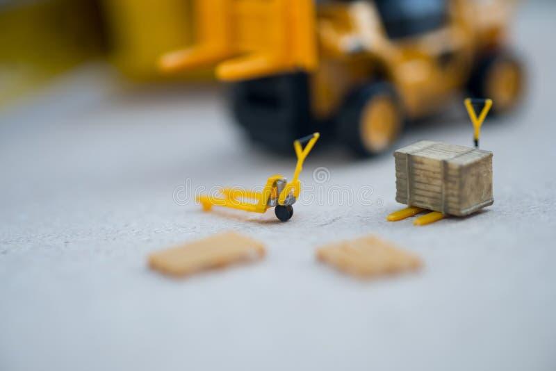 Miniatyrgul leksakgaffeltruck och miniatyrpalettlastbil arkivbild