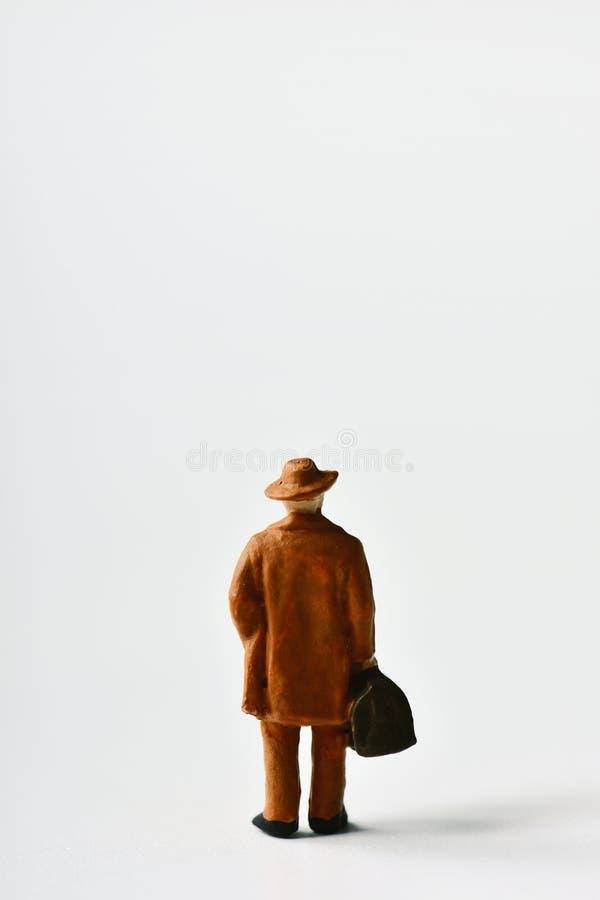 Miniatyrhandelsresandeman med en resväska fotografering för bildbyråer
