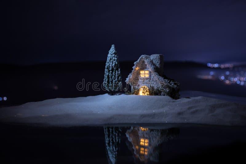 Miniatyrhus för jul och för nytt år i snön på natten med granträdet Litet leksakhus på snö med träd- och bokehstaden royaltyfri fotografi