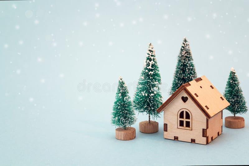 Miniatyrhus för jul och för nytt år med granträd på blått b fotografering för bildbyråer
