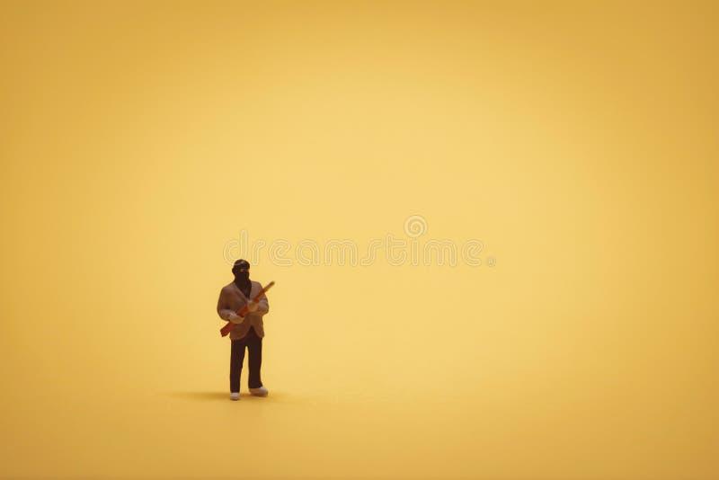 Miniatyrinbrottstjuv med hagelgeväret på gul backgound fotografering för bildbyråer