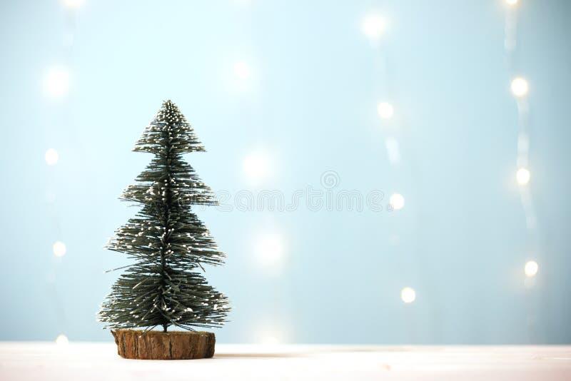 Miniatyrjulträd på trätabellen över suddighetsbokehljus - blå bakgrund arkivfoton