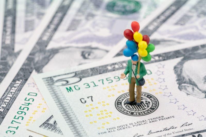 Miniatyrlycklig man som rymmer färgrika ballonger på emblem för USA Federal Reserve på US dollarsedel, som FED betraktar räntesat royaltyfri bild