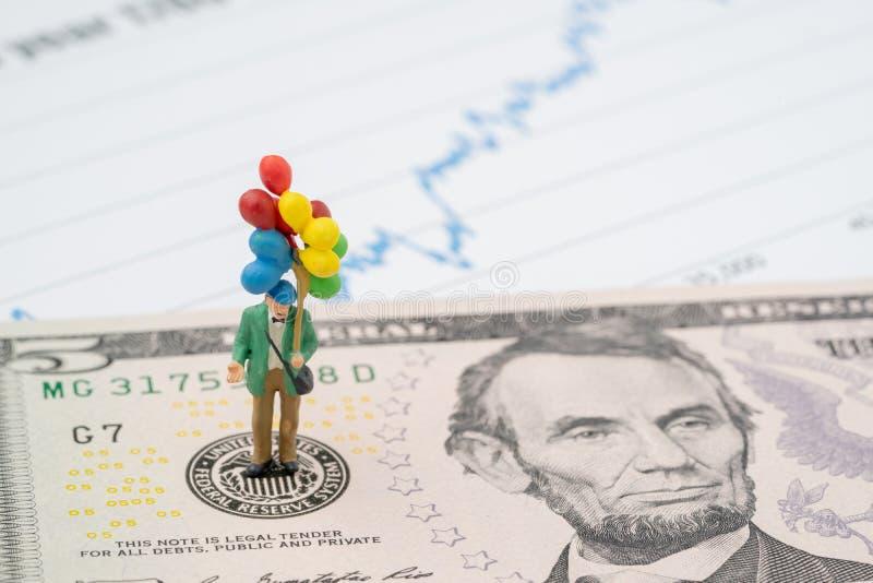 Miniatyrlycklig man som rymmer färgrika ballonger på emblem för USA Federal Reserve på US dollarsedel, som FED betraktar räntesat arkivfoton