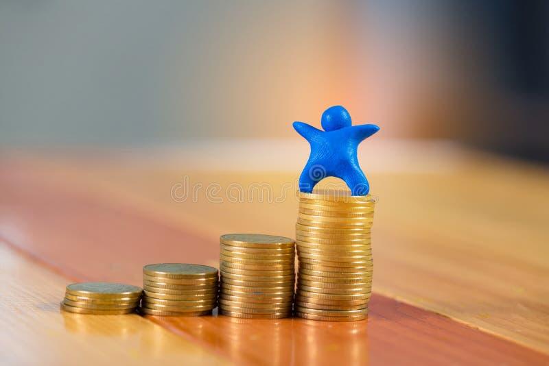 Miniatyrmänskligt diagram som göras från blå plasticine med mynt på w royaltyfria bilder