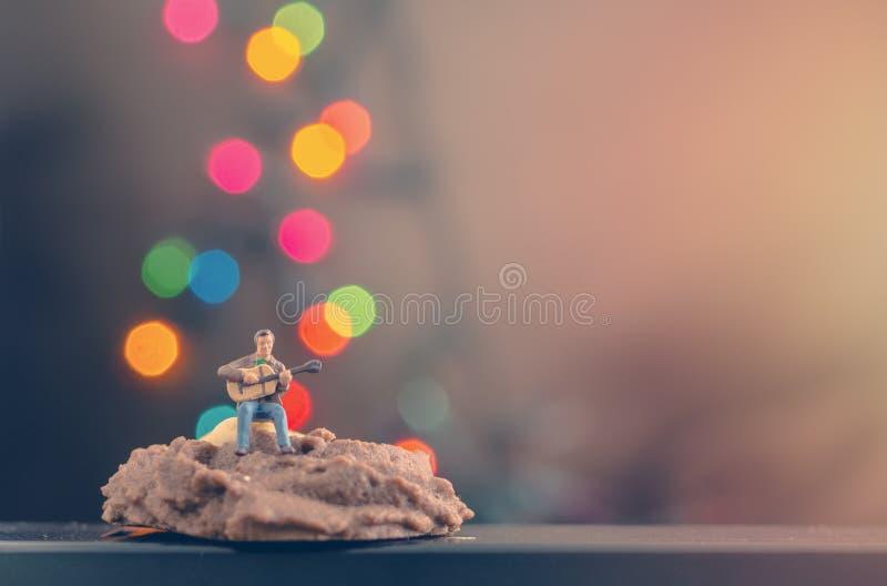Miniatyrman som spelar gitarren på kakan royaltyfria bilder