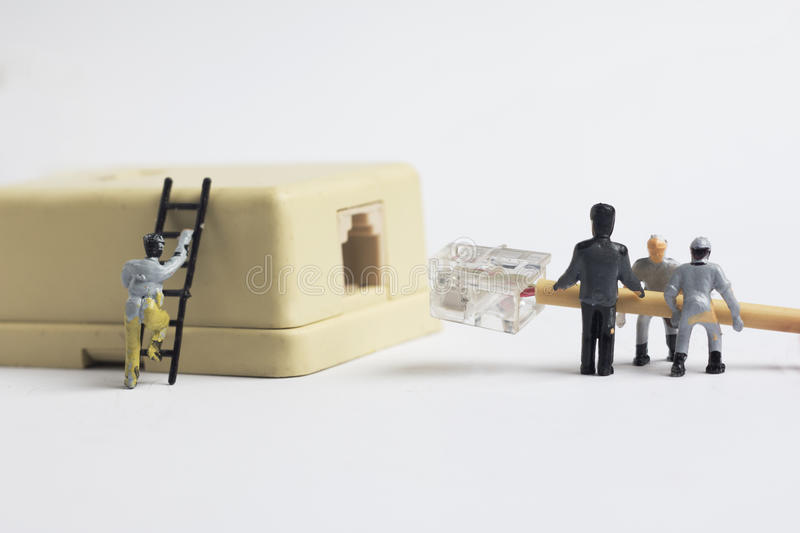 Miniatyrmannen som pluggar i telefonkabelkontaktdon royaltyfri foto