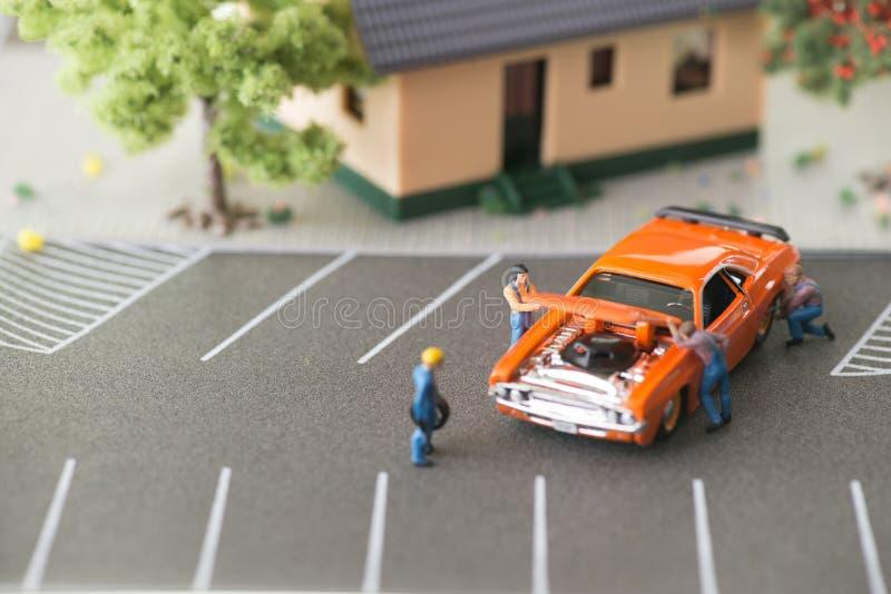 Miniatyrmekaniker som arbetar på en bil royaltyfri fotografi