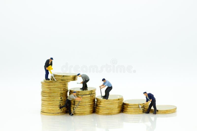 Miniatyrminiatyr: Arbetare och hjälpmedel med den guld- bunten av mynt Bildbruk för finans, affärsidé arkivfoto