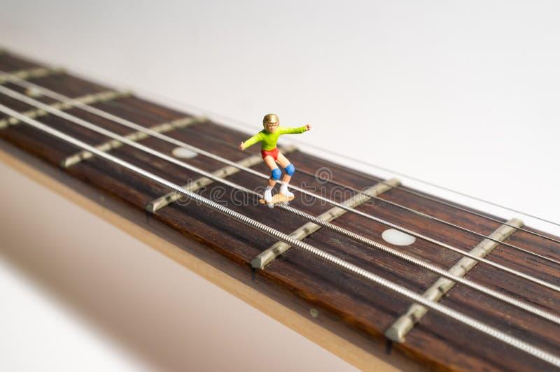 Miniatyrskateboradåkaregitarr royaltyfria bilder
