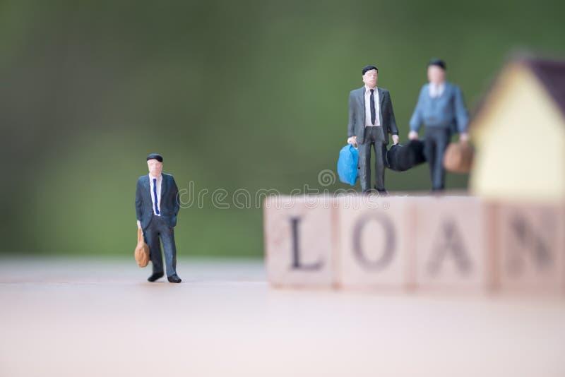 Miniatyrställning för affärsfolk på träordet LÅN royaltyfri bild