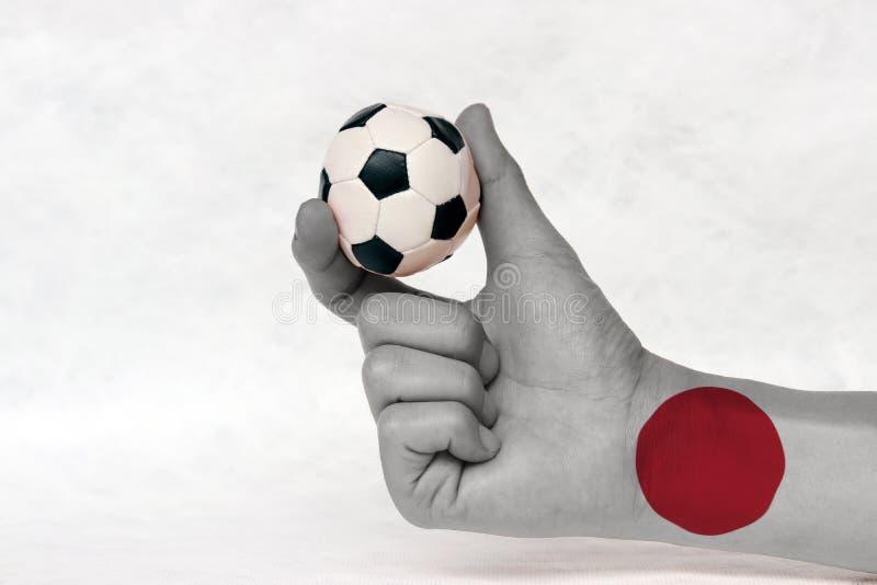 Miniball des Fußballs in gemalter Hand Japans Flagge, halten sie mit Finger zwei auf weißem Hintergrund lizenzfreies stockbild