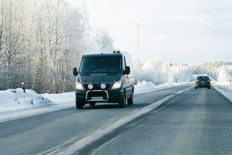Minibestelwagen op Sneeuw bos de Winterweg in Finland stock afbeeldingen