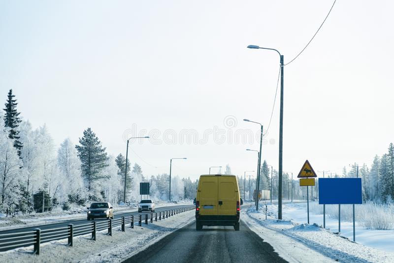 Minibestelwagen in Sneeuw bos de Winterweg in Finland stock fotografie