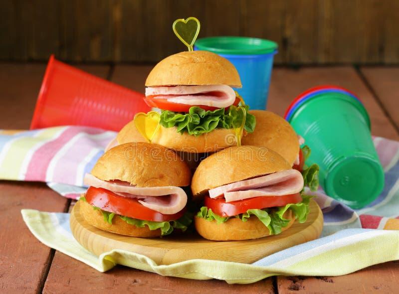 Miniburgers met ham en groenten stock afbeelding