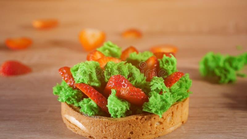 Minicake met aardbeiplakken en room bij koekje het gieten met gepoederde suiker stock afbeeldingen