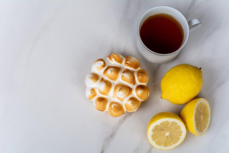 Minicitroencake, citroenen en kop thee stock afbeeldingen