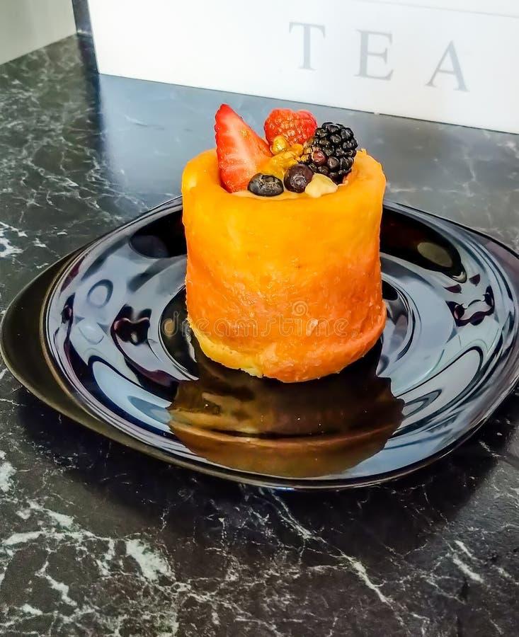 Minidiecake met verse aardbei, framboos, braambes, gouden stof, en de zomerbessen wordt verfraaid stock foto's
