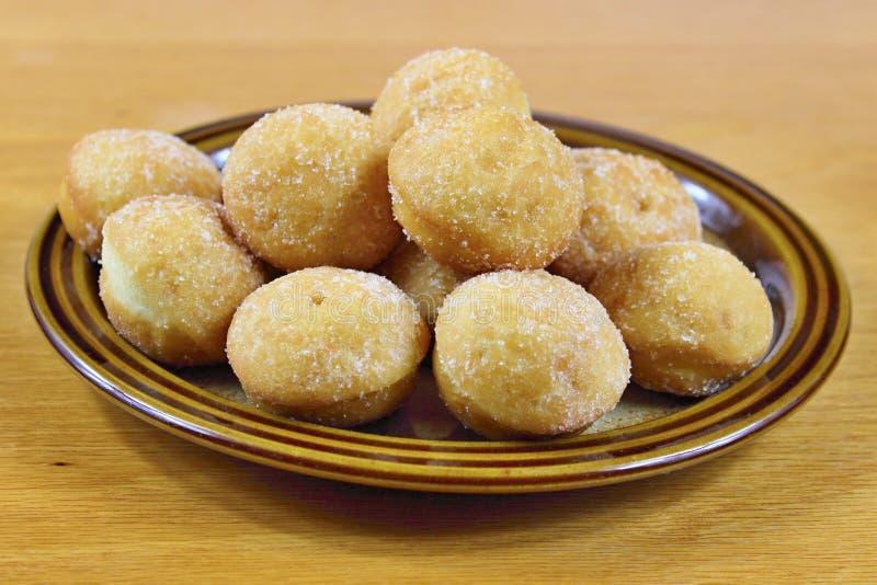 Minidonuts auf einer braunen Platte lizenzfreie stockbilder