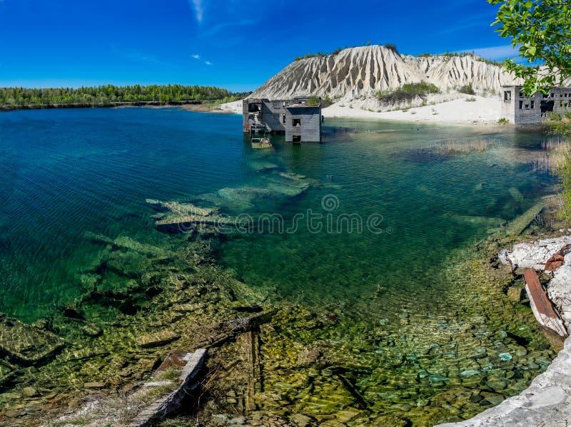 Miniere e hauses abbandonati Cava e vecchia architettura della prigione Acqua blu cristallina, lago e montagna Le dune delle cene fotografie stock