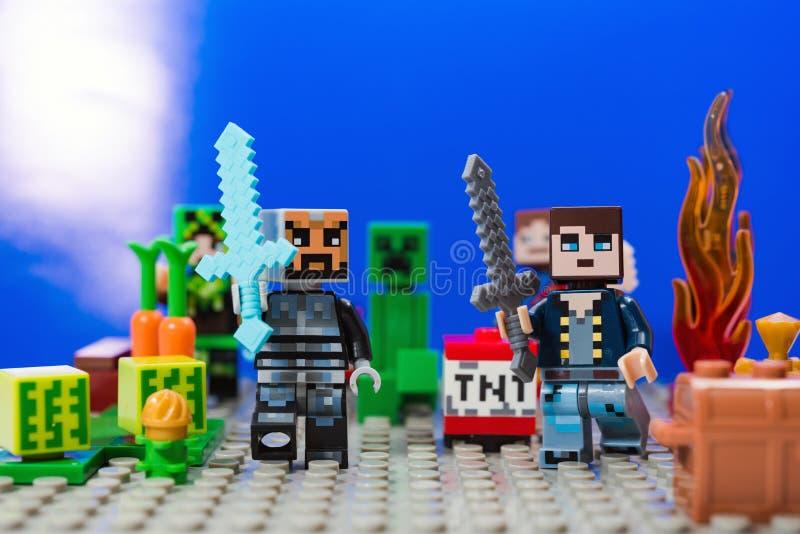 Minifigure有金刚石比赛Minecraft奔跑的剑和字符的铁人远离爬行物的 库存照片