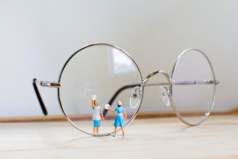 Minifigure begreppsrengöringsmedel i blått, rengörande exponeringsglas för hemmafru royaltyfria bilder