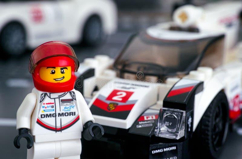 Minifigure för Lego Porsche 919 blandchaufför av Lego Speed Champions nära hans bil royaltyfri bild