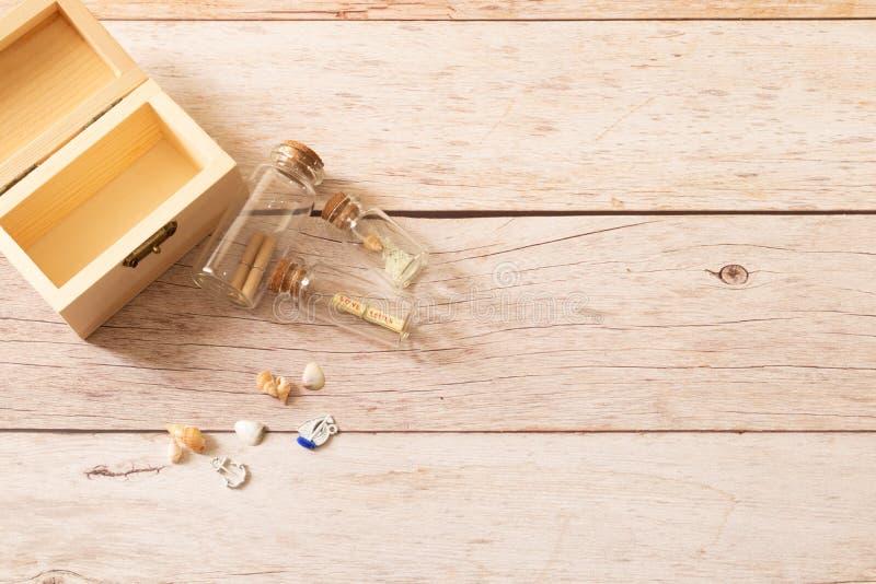 Miniflaschenglas füllt mit kleiner Rolle von Papieren und Holzkiste verzieren mit kleinen gewundenen Tritonshörnern lizenzfreie stockbilder