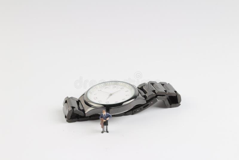 Minigeschäftsmannzahl, die auf Uhr steht stockfoto