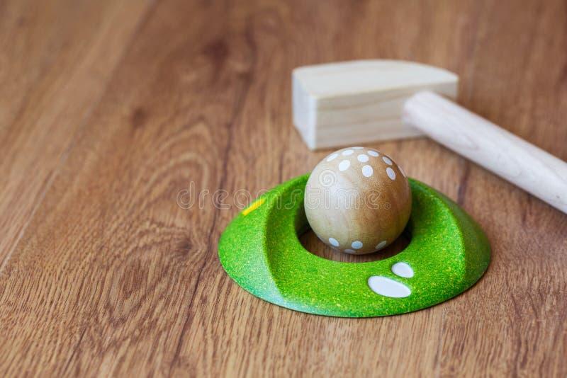 Minigolf-Holz für Kinder Golfclub und ein Ball während eines Minigolfspiels Kind-` s Spiele zu Hause lizenzfreie stockfotos